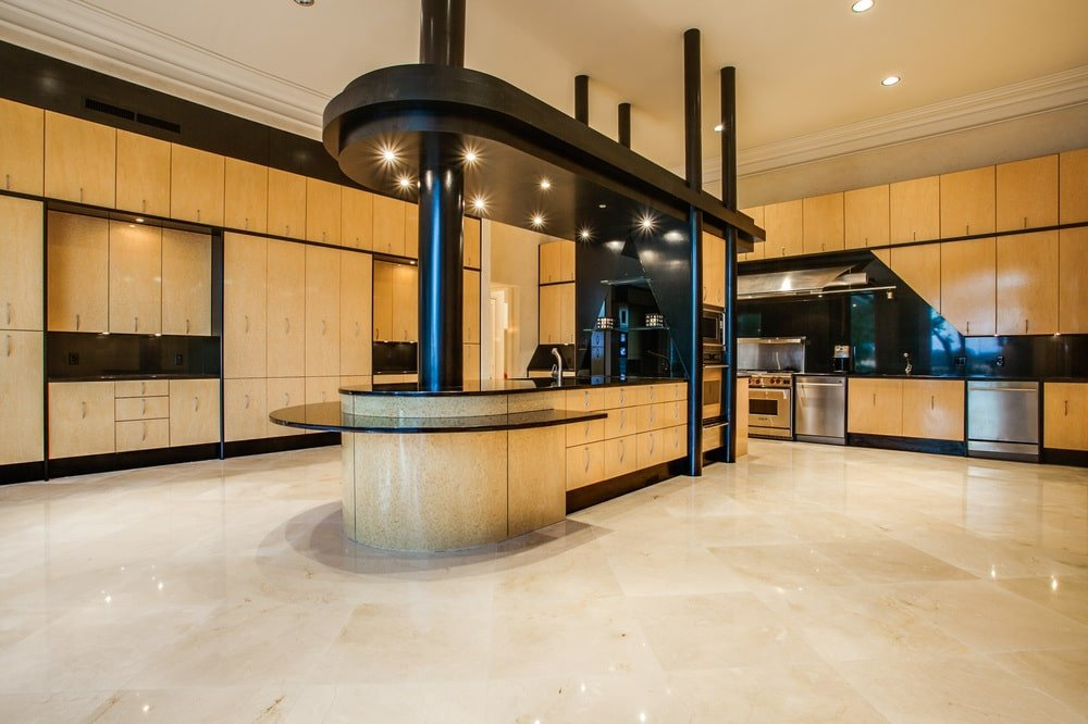 The large kitchen has a huge floor-to-ceiling structure in the middle that has an island, pillars and its own ceiling with recessed lights. This is then surrounded by cabinetry that matches the tone of the floor.