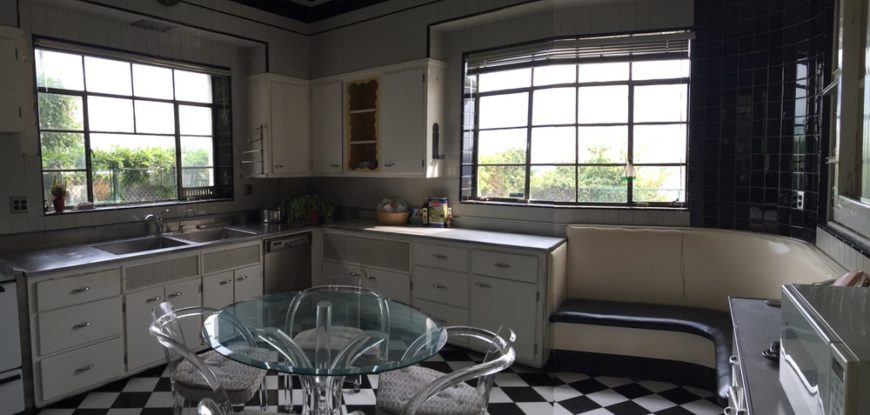 The kitchen has a black and white checkered floor that stands out against the white cabinetry and glass-top round table. There is also a built-in booth-style bench at the corner by the cabinetry.