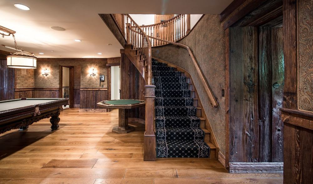Entry foyer with rustic walls and a staircase featuring carpeted steps on the side. There's a billiards table set up lighted by attractive ceiling and wall lights.