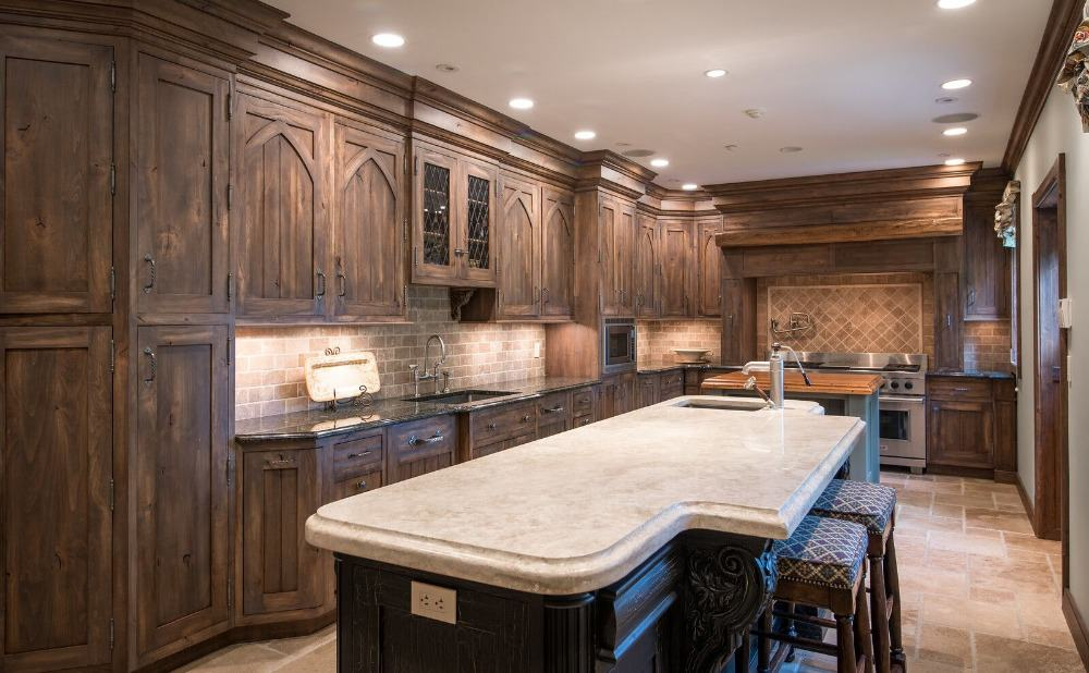 Kitchen with two islands, one is for meal preparation and one serves as a breakfast bar, featuring a marble countertop.
