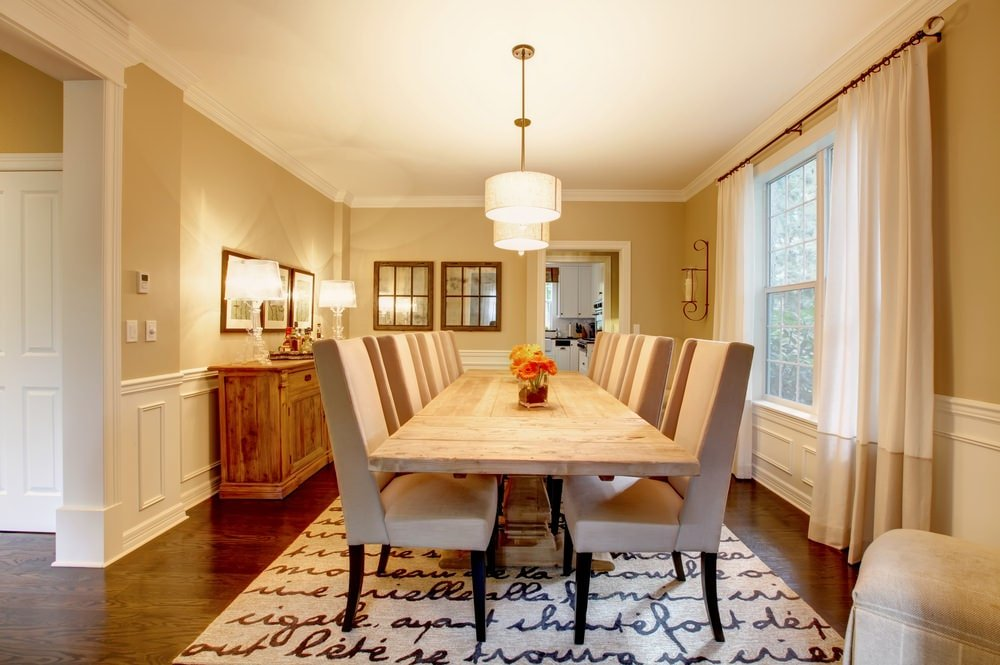 A warm dining room with taupe wingback chairs and a natural wood dining table illuminated by drum pendant lights. It has dark hardwood flooring and wainscoted walls adorned by mirrors and framed artworks.