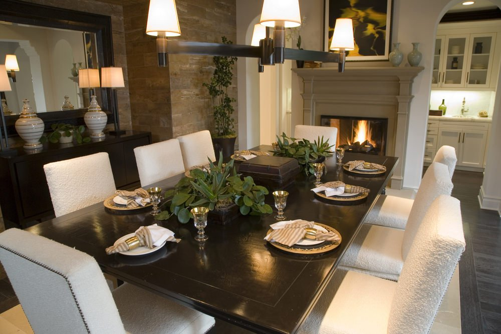 A striking artwork hangs above the taupe fireplace facing the beige upholstered chairs and a dark wood dining table lighted by a bronze chandelier. It is accompanied by a wooden buffet table that's topped with gorgeous vases and sleek table lamps.