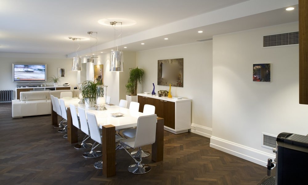 An open dining area illuminated by recessed ceiling lights and chrome pendants hanging over a sleek dining table surrounded by modern white chairs on a herringbone wood flooring. There's a buffet table across that's complemented with a mirror and potted plant.