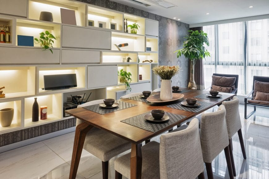 A pair of brown chairs face the wooden dining table with gray upholstered chairs in this dining room with tiled flooring and open shelving against the gray patterned wallpaper filled with various decors.