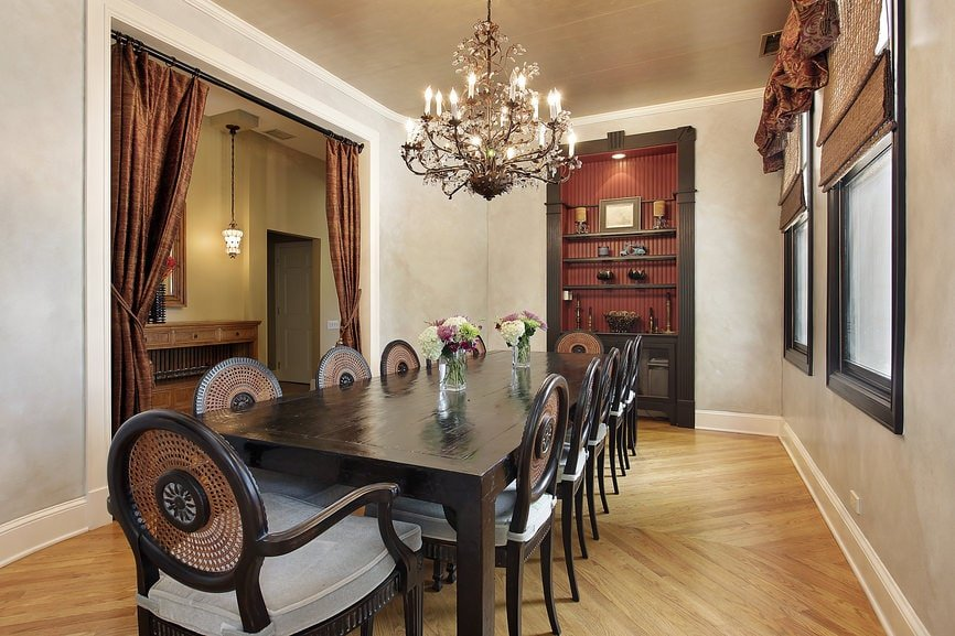 Sophisticated dining room illuminated by a gorgeous chandelier that hung over the dark wood dining table surrounded by stylish round back chairs. There's an inset shelf on the side filled with various decors.