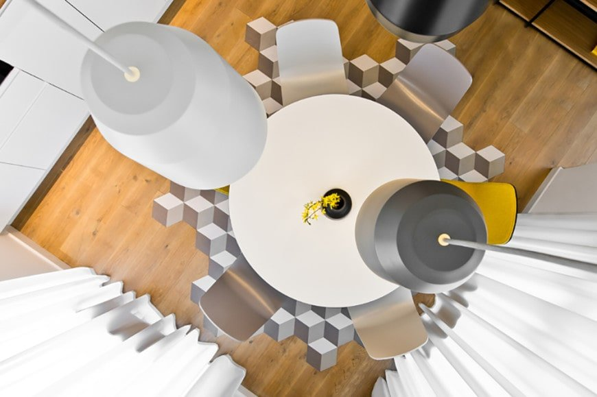 Top view of the small dining room featuring sleek pendant lights and a round dining table surrounded by modern chairs in yellow and different shades of gray.