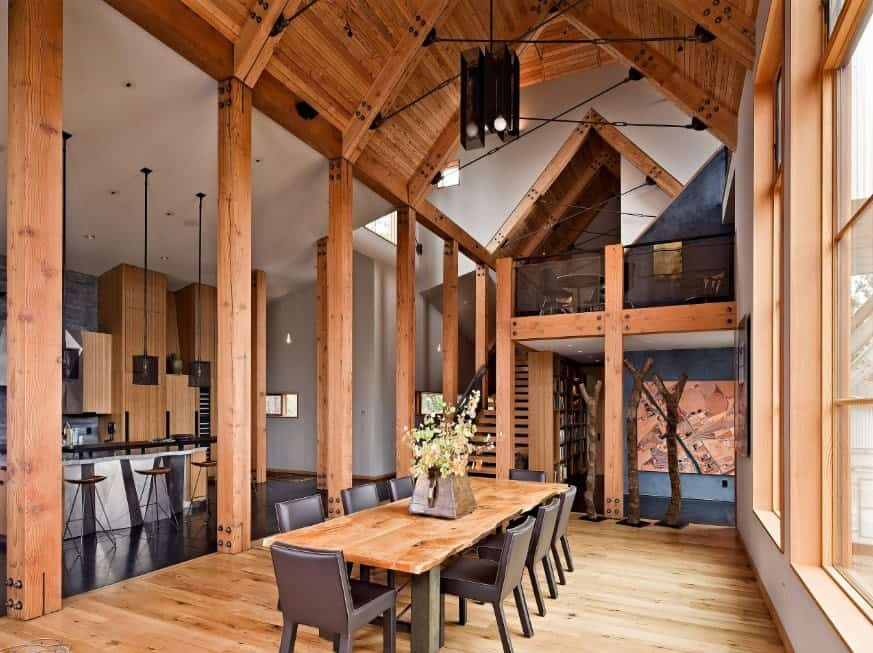 This cozy dining room is framed with wooden columns blending in with the hardwood flooring. It boasts a tall cathedral ceiling clad in wood planks.