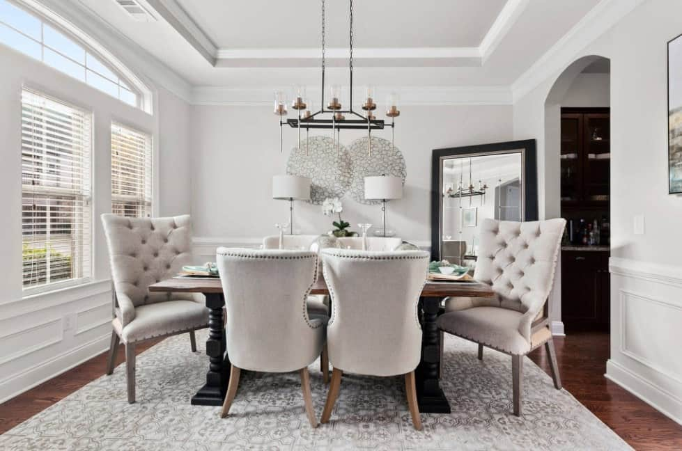 Classy dining room with dark hardwood flooring and a sleek tray ceiling that fades into the gray walls clad in crown molding and wainscoting. It is furnished with a gorgeous dining table and tufted wingback chairs over a patterned rug lighted by a wrought iron chandelier.