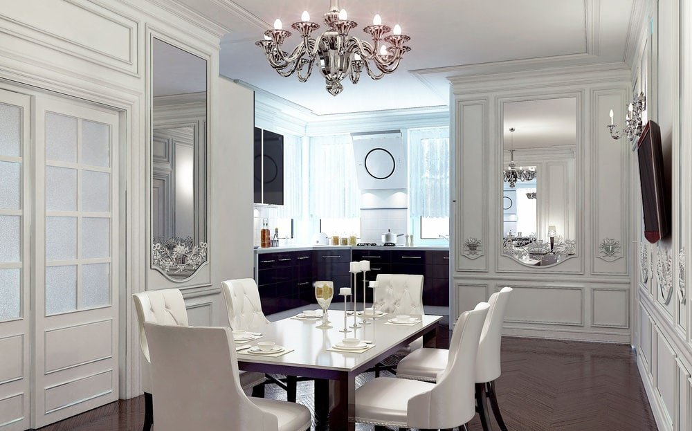 The elegant dining room boasts a chrome chandelier and classy dining set over chevron flooring. It is surrounded by white wainscoted walls fitted with inset mirrors and a flat-screen TV.