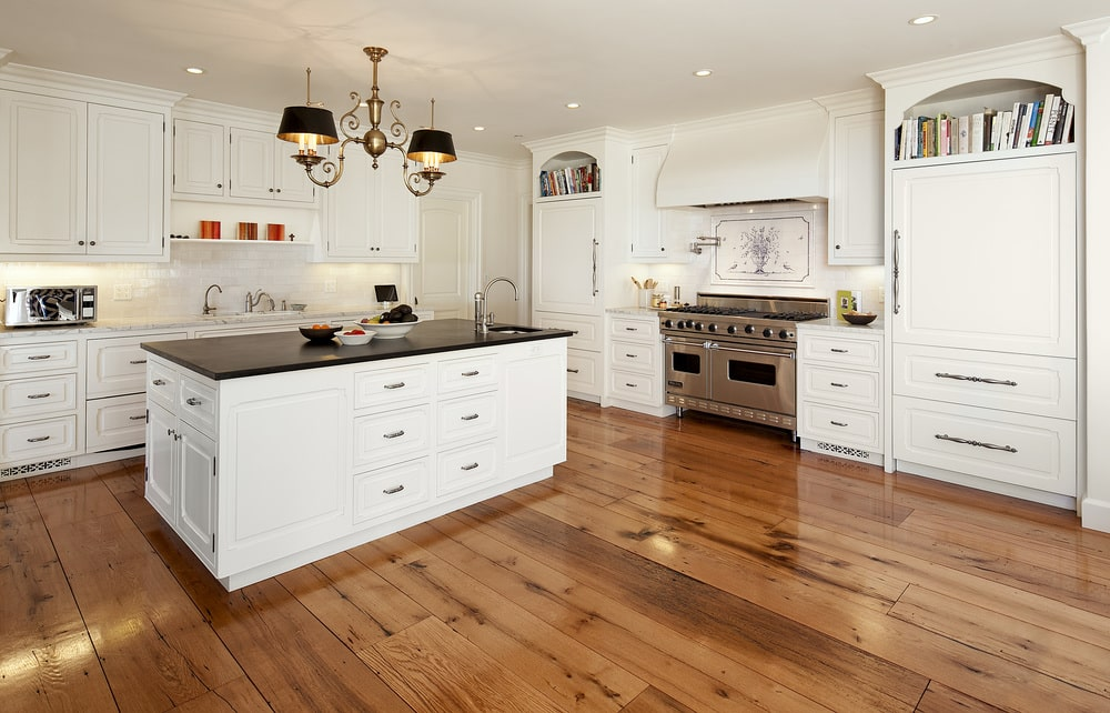 A few steps from the living room is the kitchen that has bright beige cabinetry contrasted by the black countertops and stainless steel appliances.