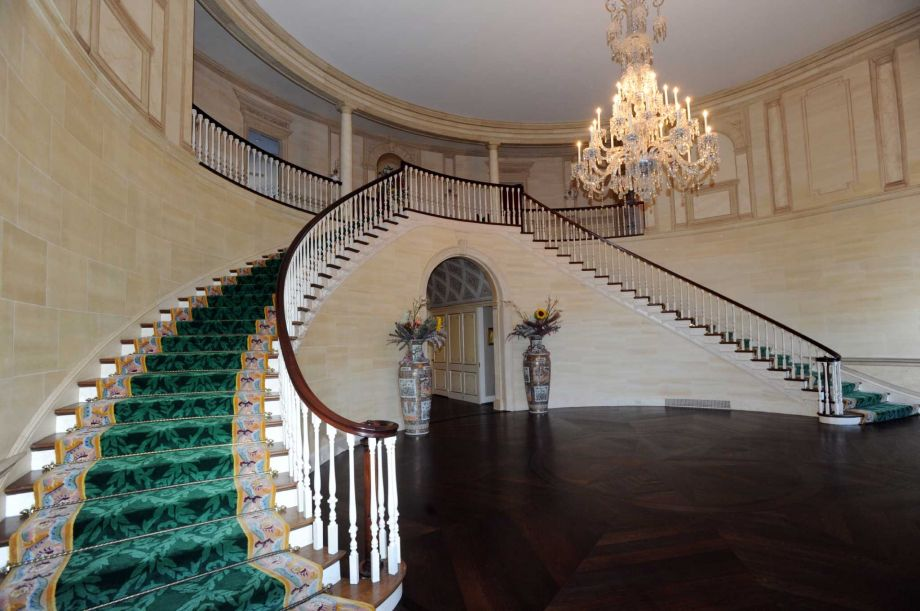 Upon entry of the house, you are welcomed by this grand foyer that has a couple of curved staircases as well as a large chandelier.