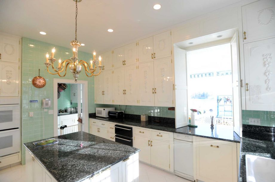 The kitchen has consistent beige tones to its cabinetry and ceiling contrasted by the black countertops and backsplash.
