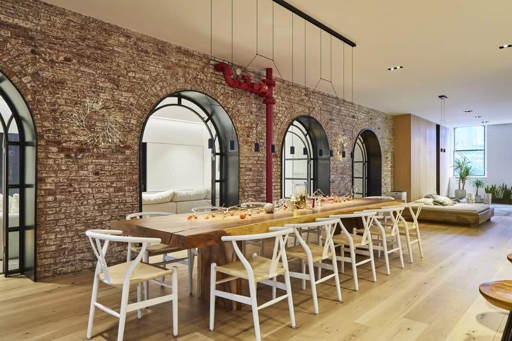 This is a close look at the dining room that has a long wooden rectangular dining table surrounded by white wishbone chairs that pair well with the hardwood flooring and red brick arches.