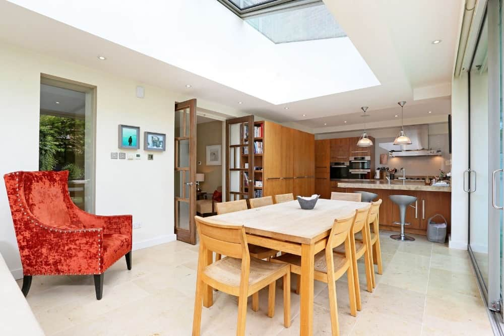 This is a large room that houses the dining area and the kitchen under one tall ceiling with skylights. The kitchen has brown wooden elements that stand out against the bright room.