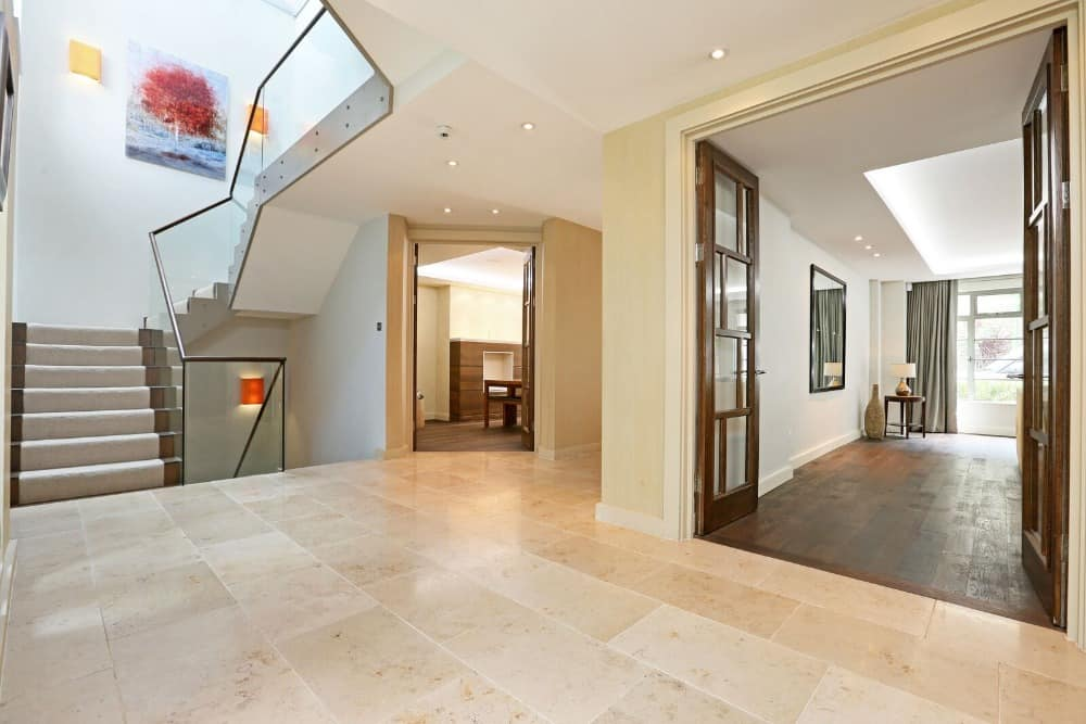This is a spacious and simple foyer with beige marble flooring that pairs well with the beige walls that lead to walkways and a modern staircase.