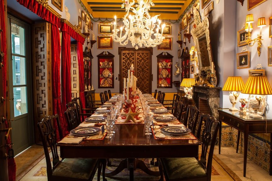 This dining room is decorated with an eclectic art gallery along with a lovely white chandelier that hung from the beamed ceiling. It has a long dining set and a fireplace flanked by brass sconces and matching table lamps that sit on dark wood tables.