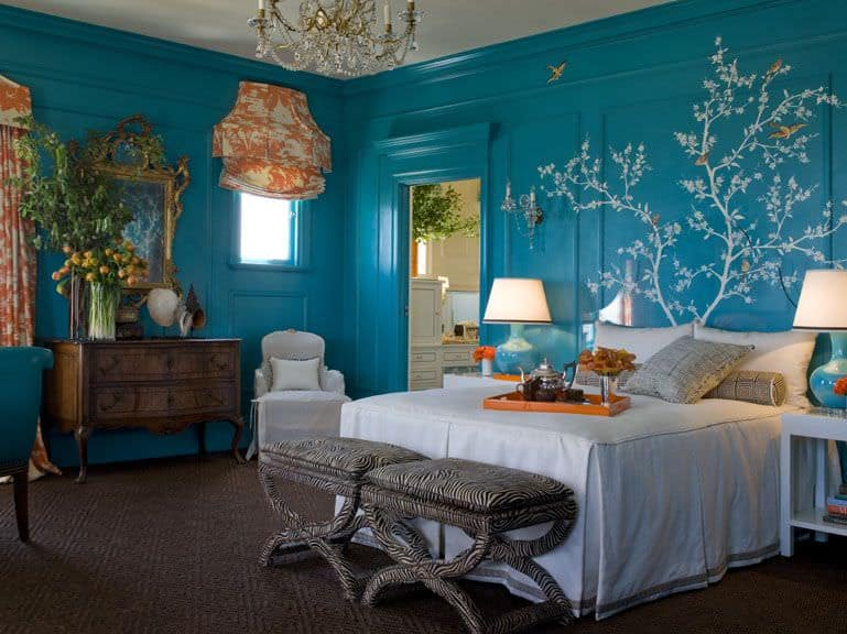 Blue wainscoted walls painted with a floral mural surrounds the eclectic furniture in this primary bedroom with textured carpet flooring and glazed windows dressed in orange patterned drapes and roman shade.