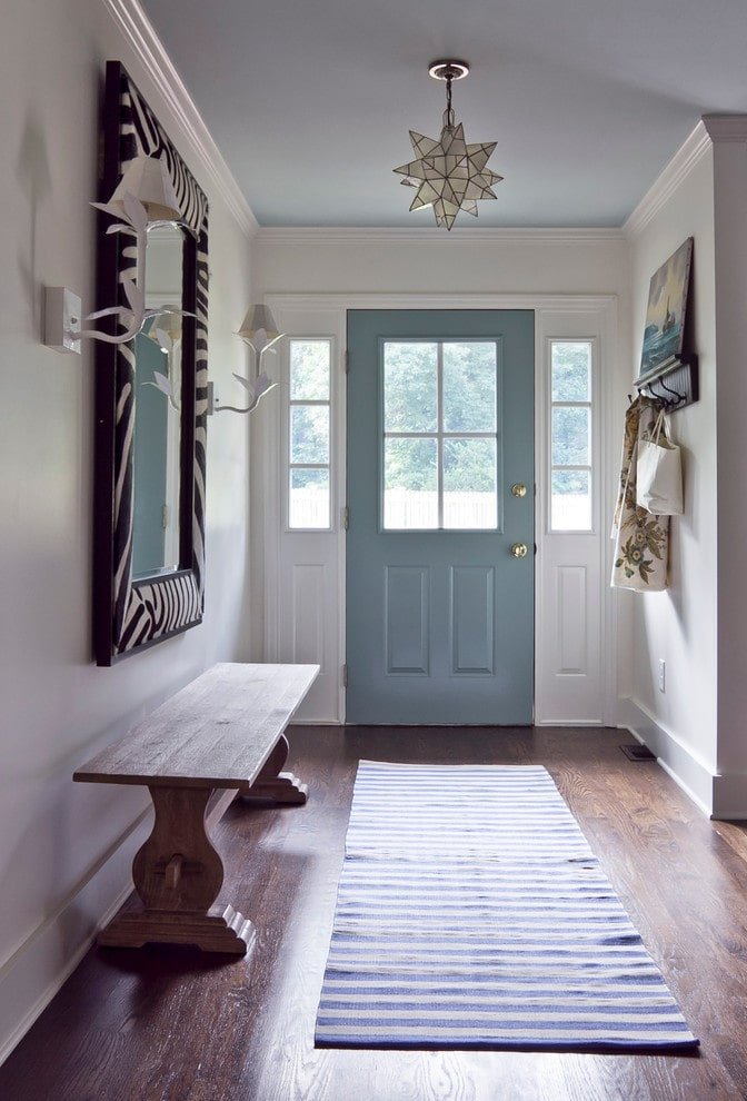 Floral sconces flanked a zebra print mirror that's fixed above a wooden console table blending in with the hardwood flooring topped by a striped runner. This foyer boasts a star pendant light and a blue front door that stands out against the white walls.