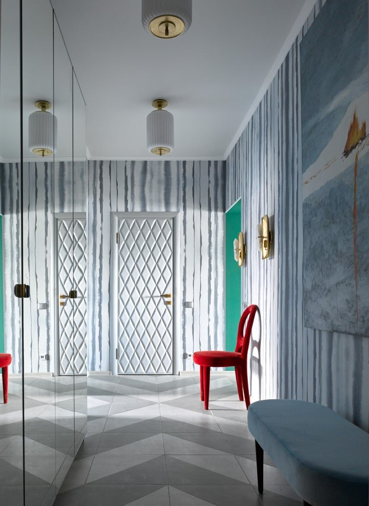 A red velvet chair stands out in this eclectic foyer with striped wallpaper and a white front door arranged in a diamond pattern. It includes mirrored cabinets facing the large painting and a blue cushioned seat over gray tile flooring.