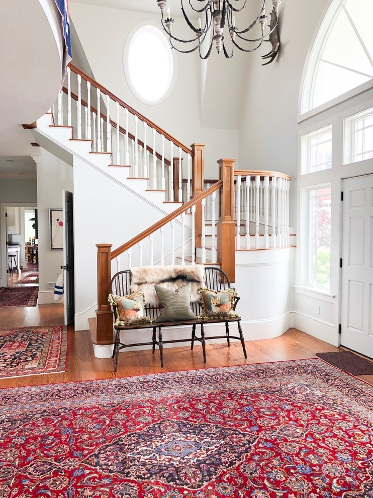 Natural light flows in through the glazed windows and panels surrounding the white front door that blends in with the white walls. This foyer offers red patterned rugs and a cozy seat illuminated by an eccentric chandelier.