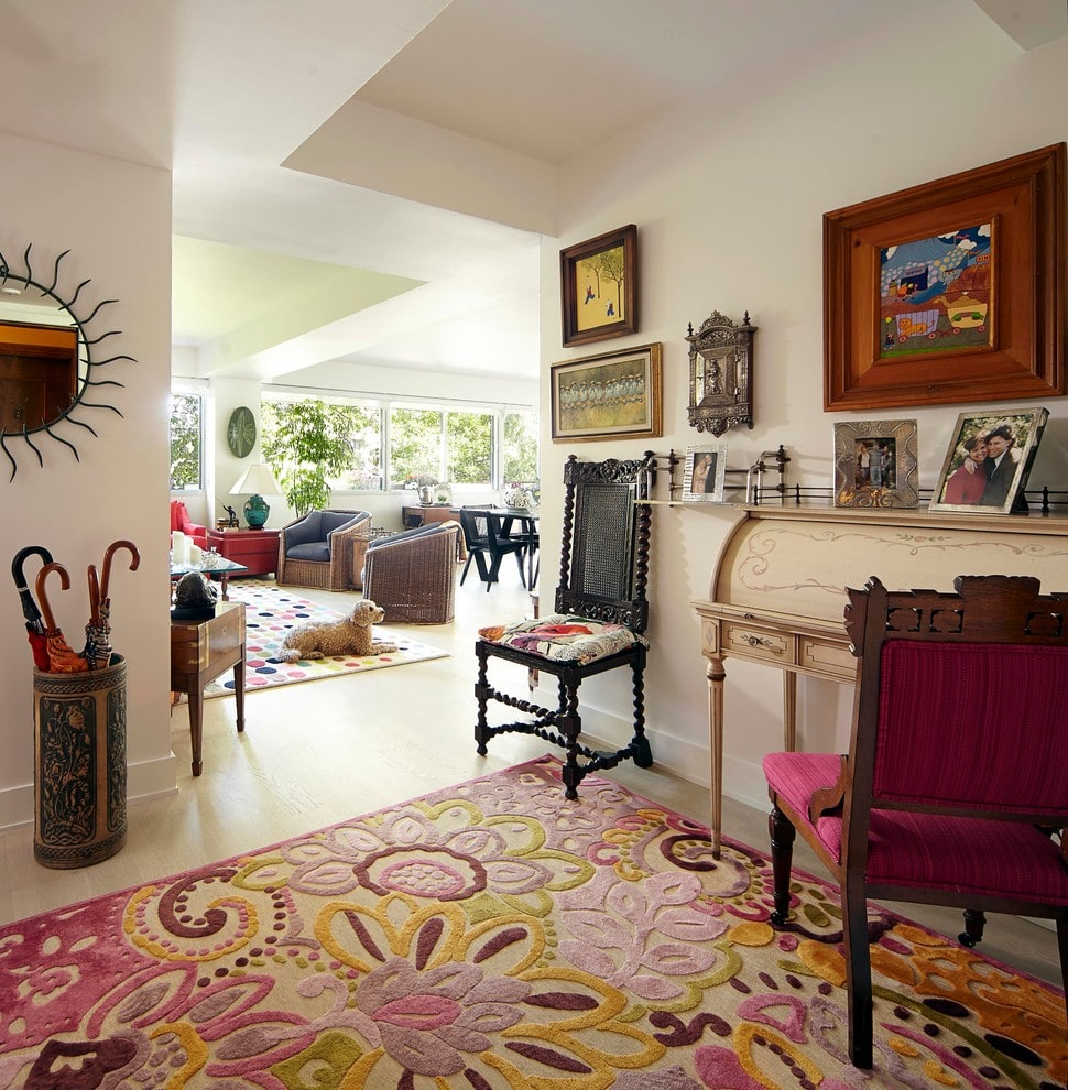 A charming floral rug adds a nice accent in this foyer decorated with a sunburst mirror and eclectic art gallery fixed on the white walls. It boasts an intricate umbrella rack and mismatched chairs complementing the beige table.