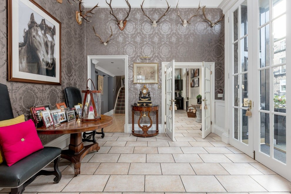 Eclectic style foyer with antler heads up on the wall, interior wallpaper, a seating area with a large side table full of photo frames, French doors, and tile flooring.