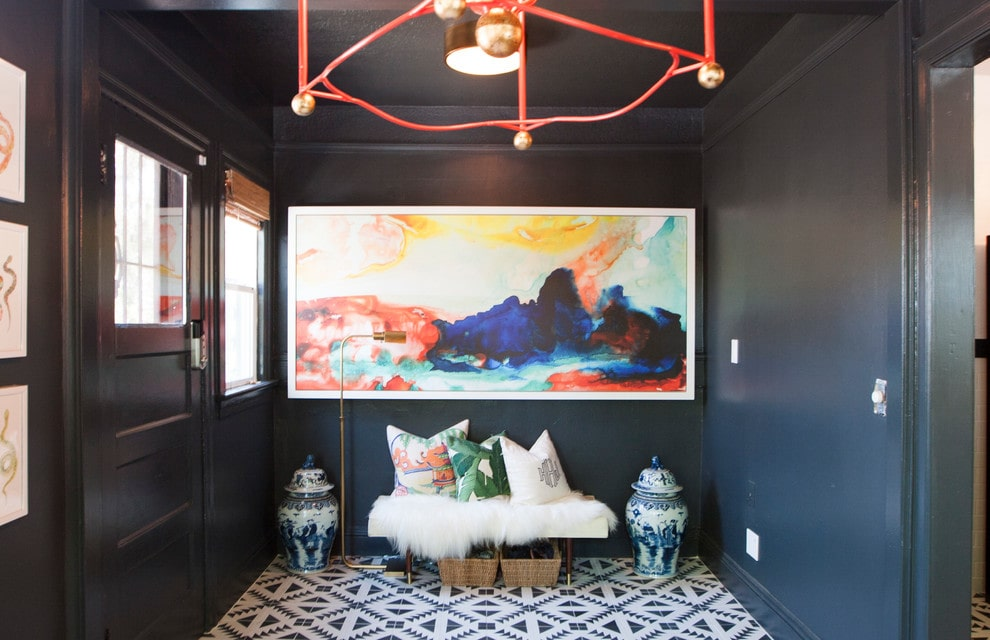 A colorful painting stands out against the black walls and front door that's fitted with a glass panel. This foyer is filled with ceramic vases and a white bench with rattan baskets underneath.