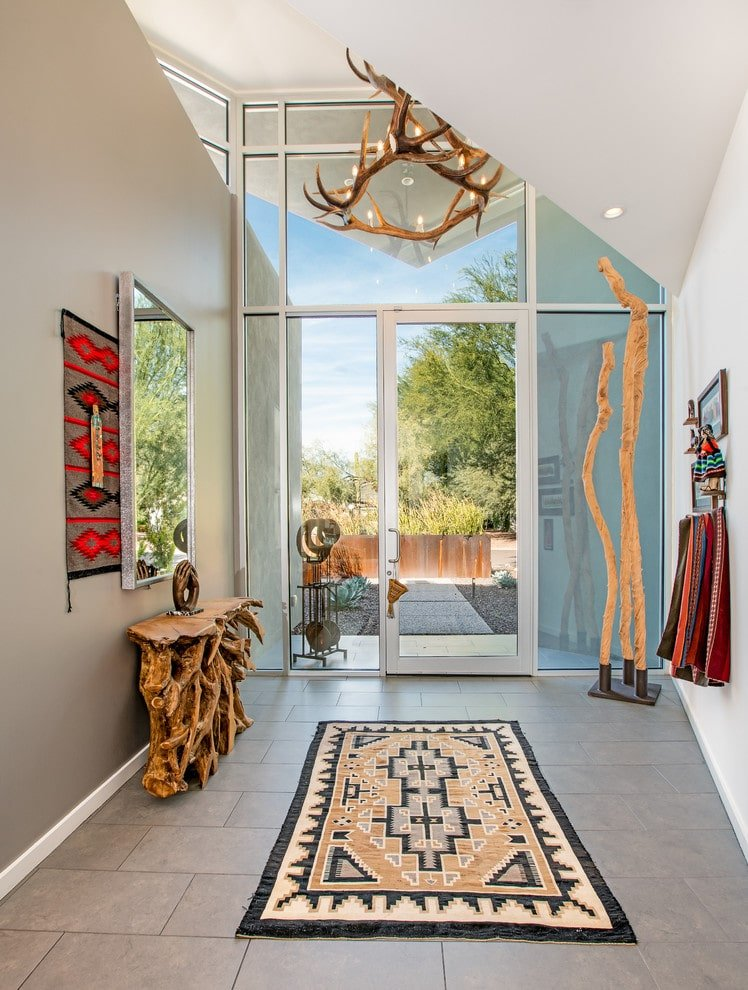 Airy foyer with tiled flooring and full height glazing inviting an abundance of natural light in. It features a stump console table and a tribal rug illuminated by an antler chandelier.