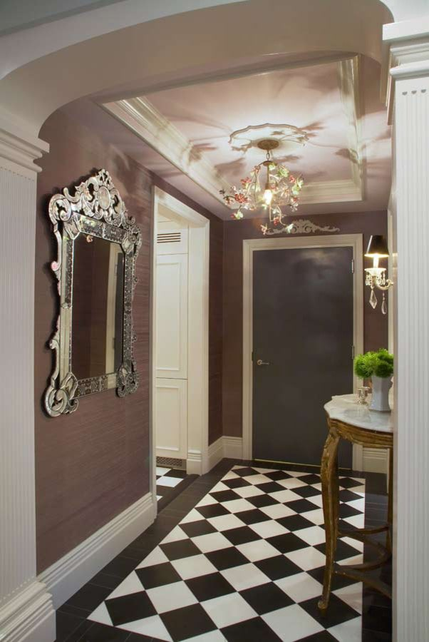 Eclectic foyer with checkered flooring and beige walls adorned by a gorgeous chrome framed mirror. It is illuminated by black sconces and a charming chandelier that hung from the tray ceiling.
