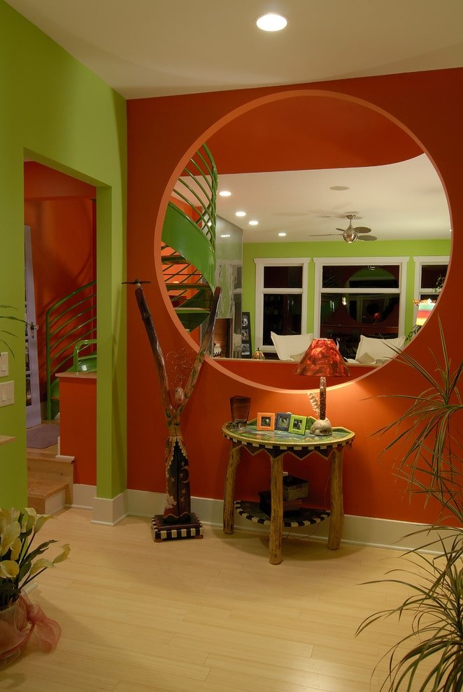A tropical plant creates a refreshing ambiance in this foyer with light hardwood flooring and vibrant multi-colored walls in green and orange. It is filled with a lovely wooden sculpture and a semi-circular console table topped with photo frames and a unique table lamp.