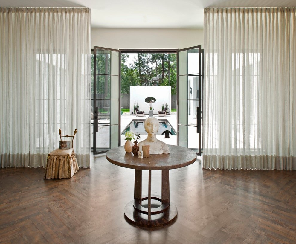 Classic foyer with French entry door and windows covered in sheer draperies. It is filled with a skirted chair and a round center table with a bust sculpture on top over herringbone wood flooring.