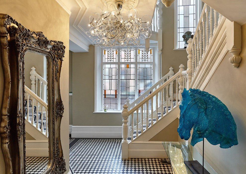 A statement chandelier illuminates this foyer along with natural light flowing in from the stained glass windows. It is decorated with a large carved wood mirror and a blue horse head decor that sits on a glass top console table against the beige staircase.