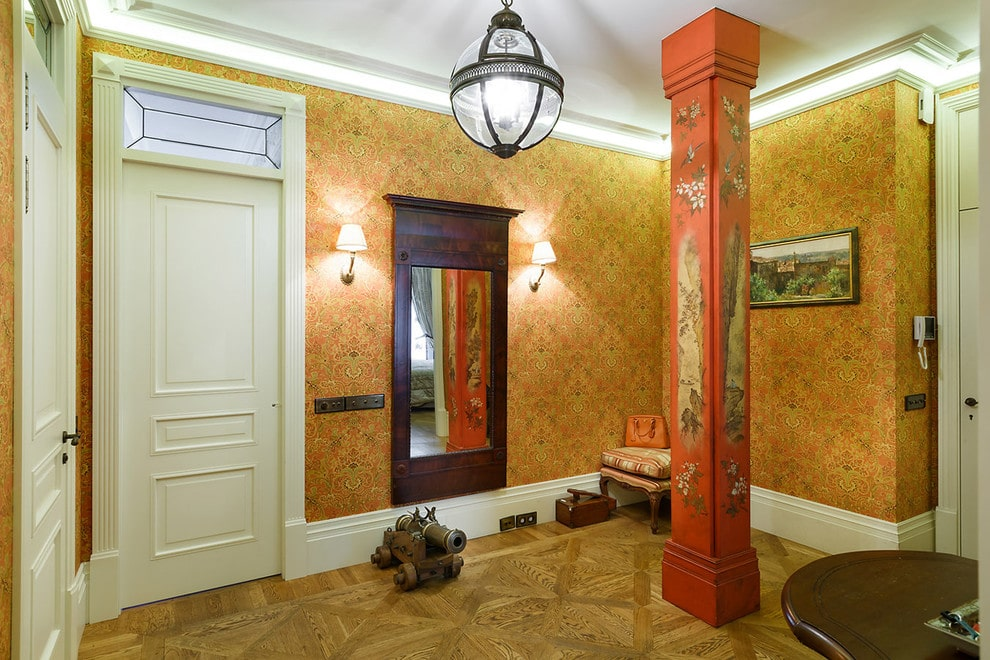 Eclectic style foyer supported by a red column that's designed with lovely murals. It is filled with a spherical pendant and striped cushioned stool along with a wooden table that matches the full-length mirror flanked by classic sconces.