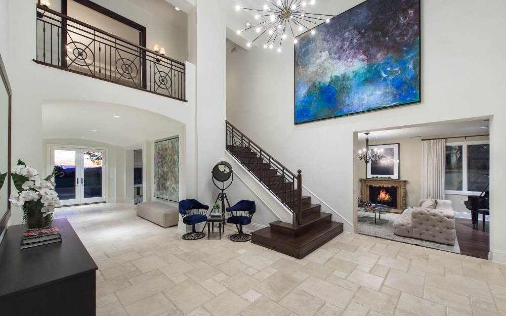 This is the spacious and bright foyer that has tall white walls adorned with a large colorful painting and a tall bright ceiling that hangs a brilliant decorative chandelier over the area.