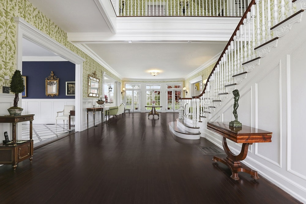 Upon entry of the house, you are welcomed by this foyer that has a dark hardwood flooring to contrast the white walls adorned with wallpaper.