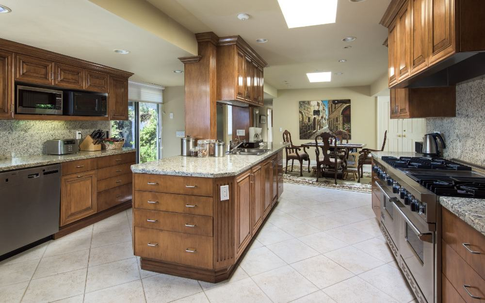 Large kitchen area featuring gorgeous marble backsplash and countertop. There's a dining table and chairs set on the side.