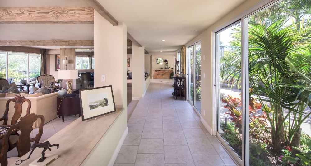 This is the lovely foyer of the house that leads you directly to the living room area. This foyer has bright glass walls with console tables on the sides.