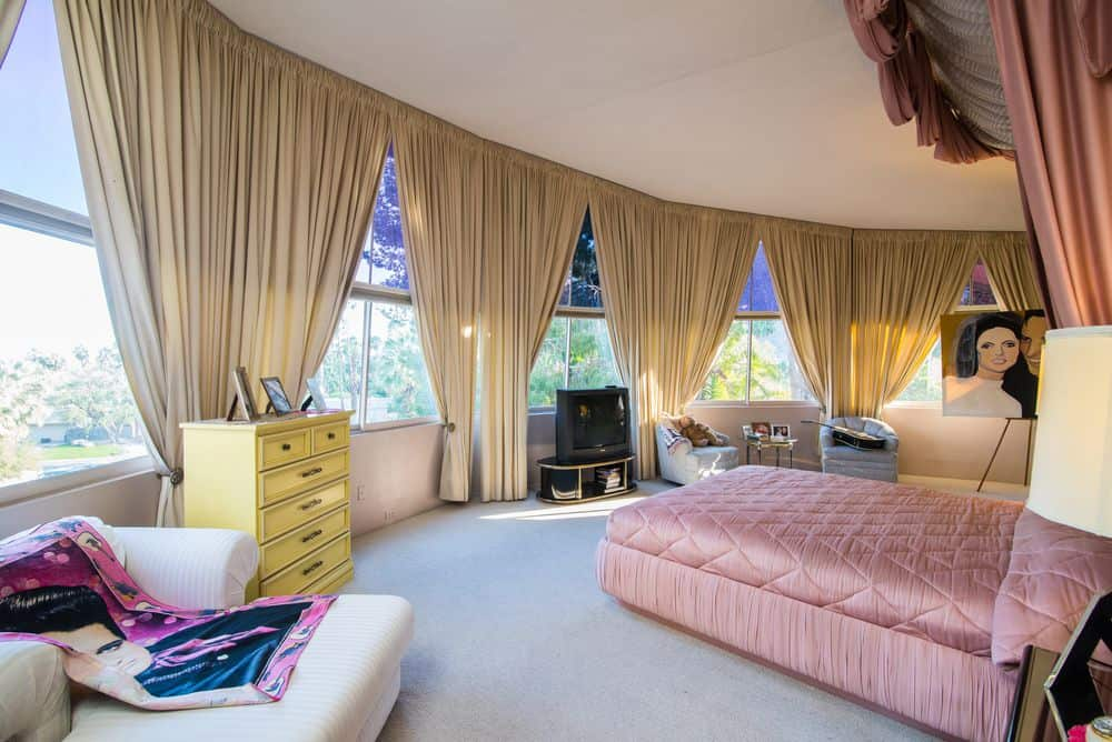 This is the primary bedroom with its spacious and bright round room surrounded by surved glass walls fitted with curtains for privacy. In the middle sits the large platform bed with sittings areas on the sides by the glass walls.