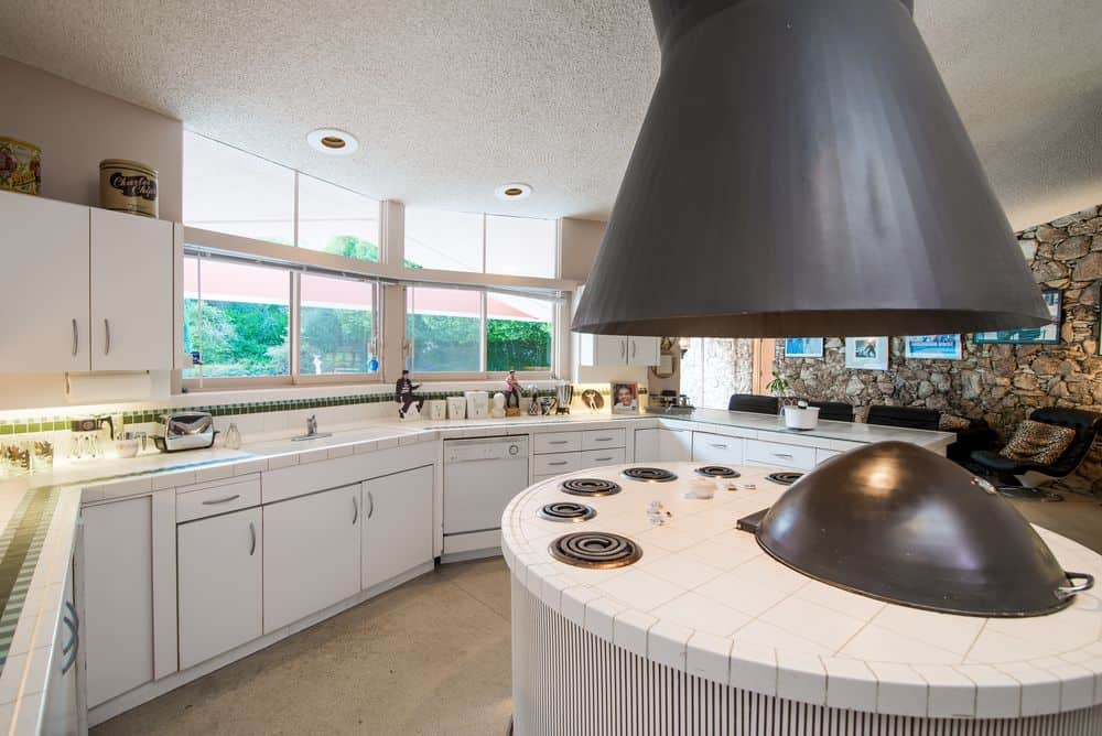 This is the gorgeous kitchen with a large circular kitchen island in the middle that houses the cooking area topped with a large dark brown vent hood that stands out against the bright elements of the room like the ceiling and surrounding cabinetry that are illuminated by the row of seamless glass walls.