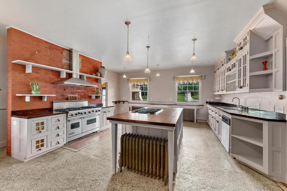 The kitchen has a large kitchen island in the middle with a dark wooden countertop. this is then topped with multiple pendant lights hanging from the bright ceiling.