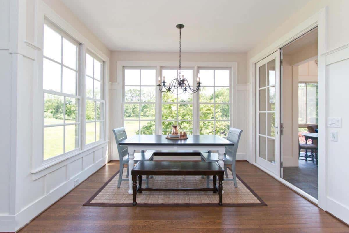 Light and airy dining room with natural hardwood flooring and white framed windows overlooking the lush greenery. It is filled with a wrought iron chandelier and a wooden dining table surrounded by gray chairs and dark wood benches over a jute rug.