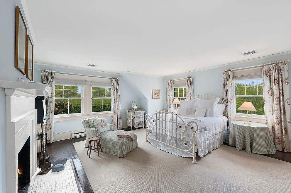 Floral draperies add charm in this farmhouse primary bedroom offering an ornate metal bed and a checkered chaise lounge matching with the nightstand's cover. It is accompanied by a white fireplace with wooden framed artworks on top fixed against the sky blue walls.