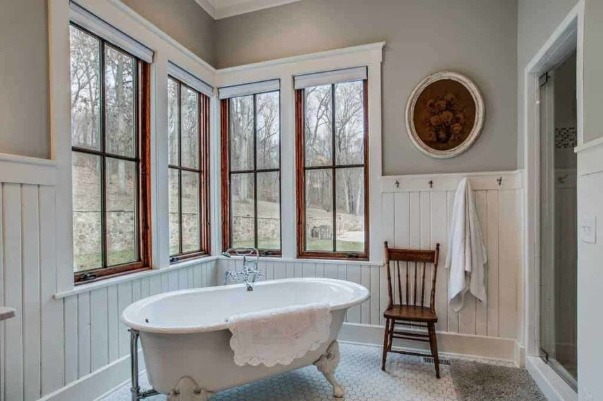 This farmhouse style master bathroom offers a freestanding tub and a walk-in shower room. The area features gray walls and glass windows.