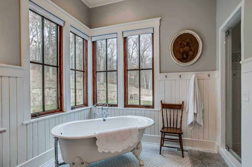 This farmhouse style primary bathroom offers a freestanding tub and a walk-in shower room. The area features gray walls and glass windows.
