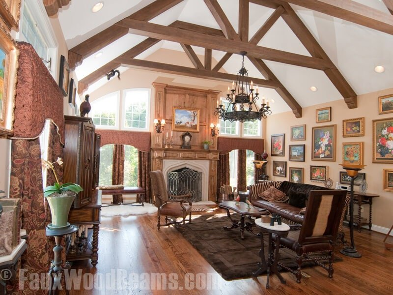Cozy living room decorated with floral gallery and a two-tier wrought iron chandelier that hung from the high ceiling framed with faux wood beams. It is filled with leather seats and a fireplace lighted by classic sconces.