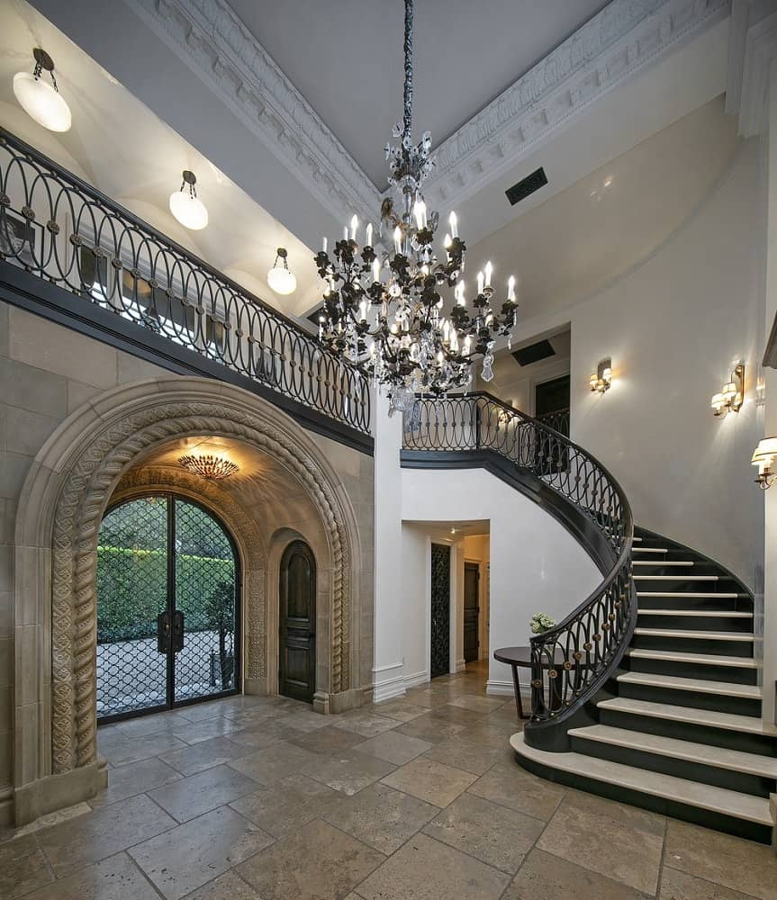 A main entry foyer of the house boasting a glamorous grand chandelier. The curved staircase is lighted by wall lights.
