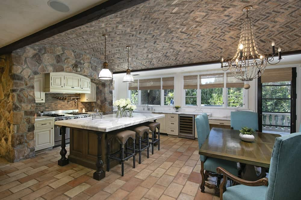 Dine-in kitchen featuring brick tiles flooring and a stunning arch ceiling. There's a large center island with a marble countertop, with space for a breakfast bar.