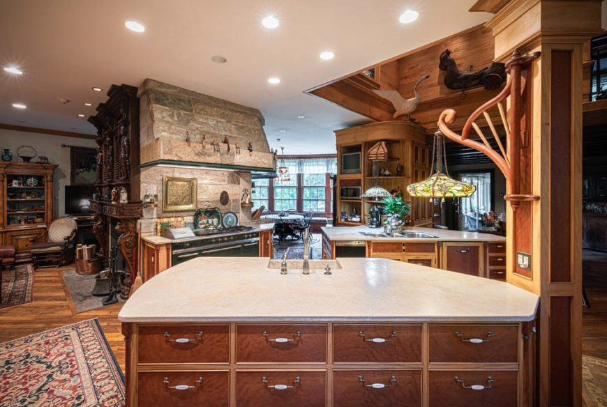 This is the large with a couple of kitchen islands and a cooking area attached to a large stone pillar. These are complemented by the wooden cabinetry and pillars.