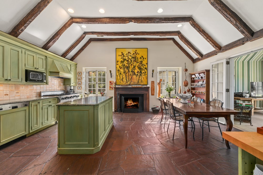 The kitchen has a cove ceiling with exposed wooden beams that match the hardwood flooring contrasted by the green kitchen island and cabinetry.