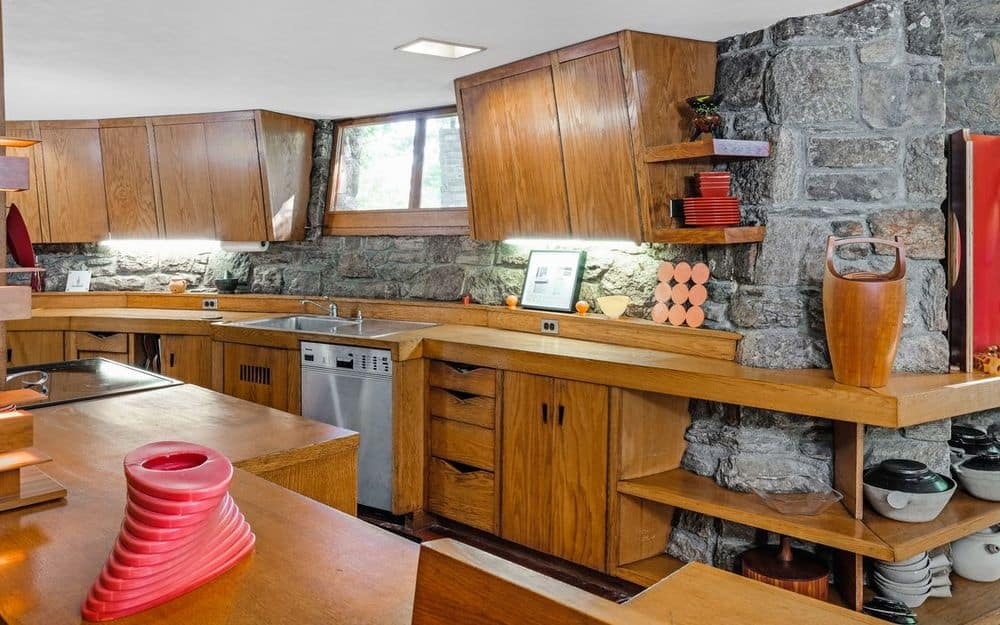 This charming kitchen has gorgeous wooden structures built into the stone walls for a lovely complement. These wooden structures also house the stainless steel appliances that stand out against the wooden elements.